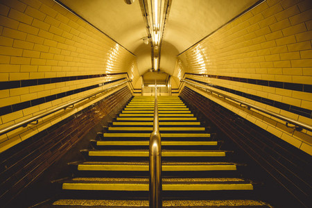 Moody yellow tunnel and staircase on London underground