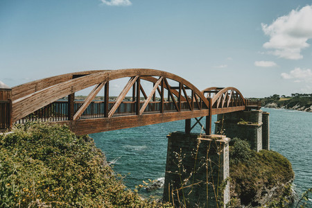 landscape with a wooden bridge over the sea in ribadeo spain