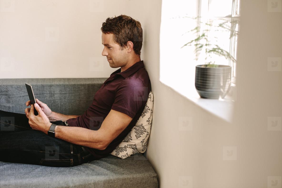 Freelancer looking at a digital tablet sitting at home