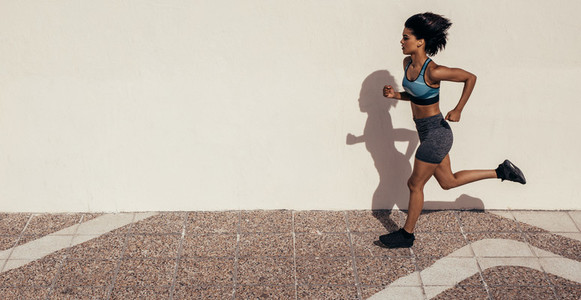 Healthy woman athlete running outdoors