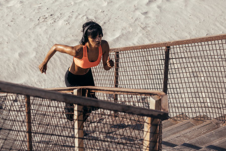 Runner climbing steps on the beach