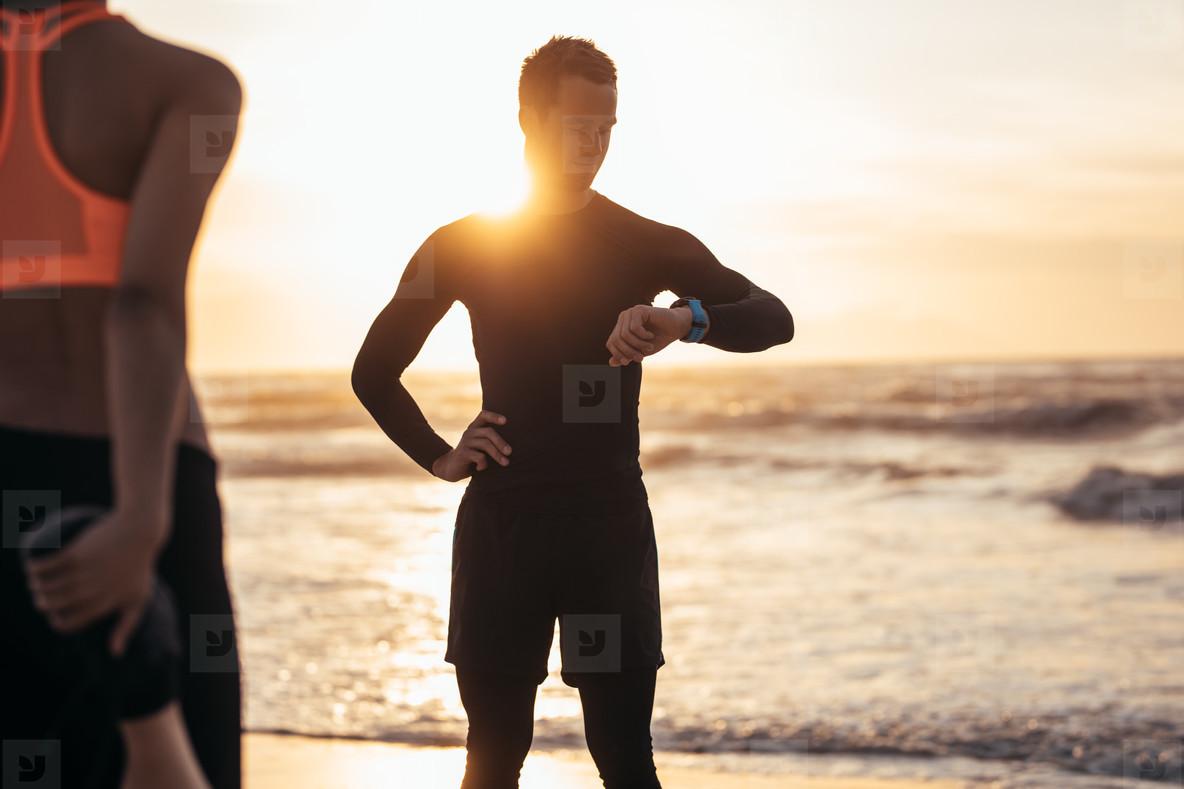 Trainer monitoring progress of a woman exercising at beach