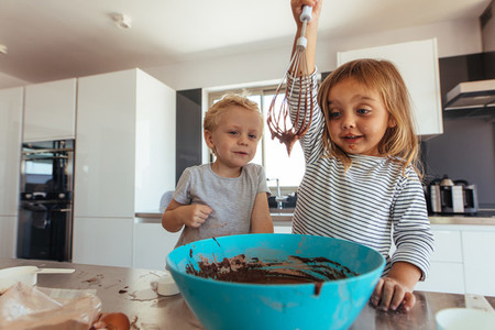 Kids preparing cake batter in kitchen