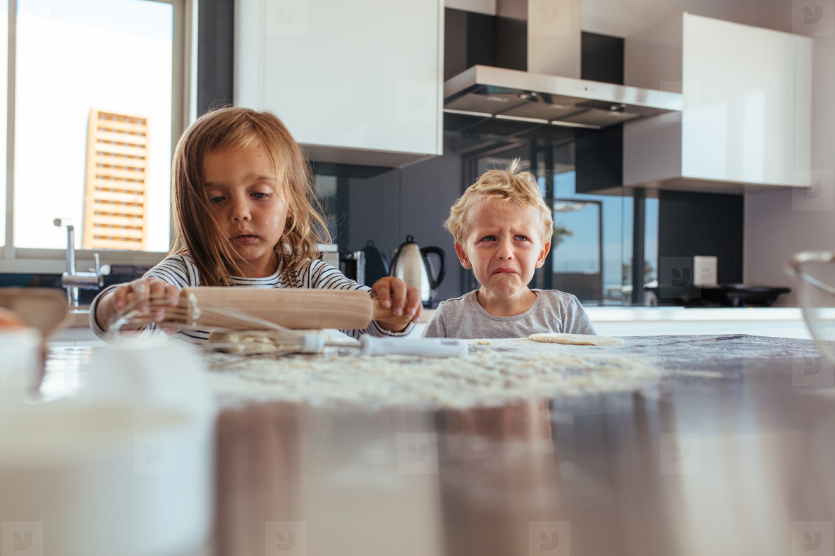 Little girl making cookies and boy crying in kitchen