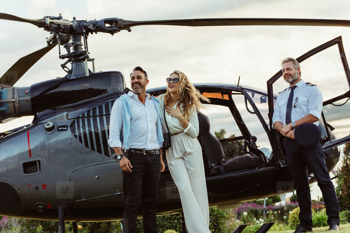 Couple standing by a helicopter with pilot