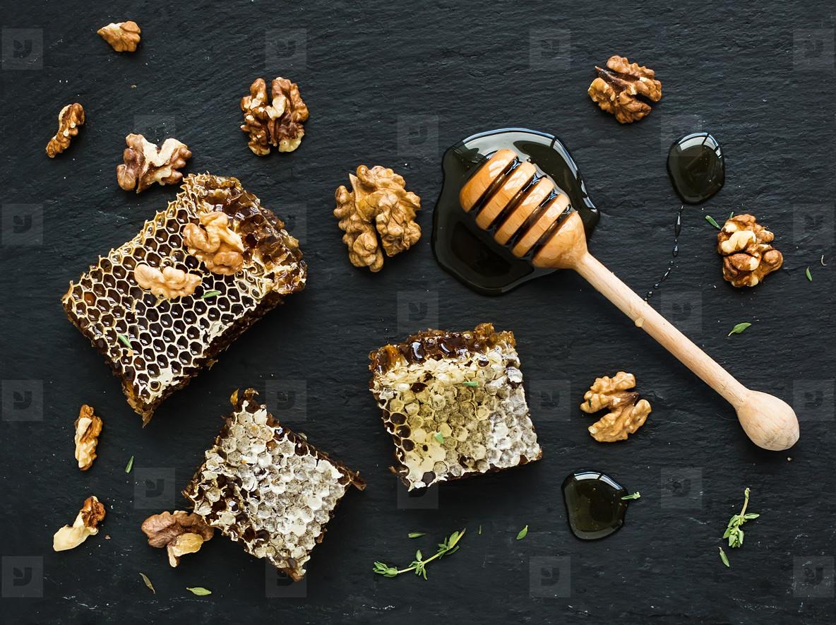 Honeycomb  walnuts and honey dipper on black slate tray over grunge dark backdrop