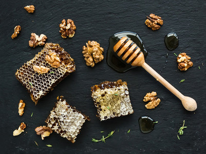 Honeycomb  walnuts and honey dipper on black slate tray over grunge dark backdrop