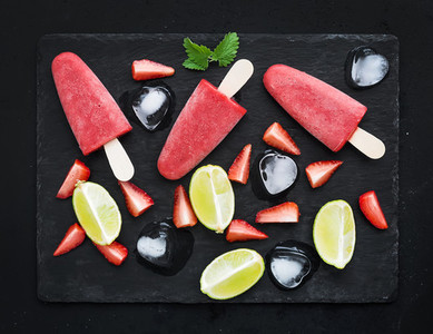 Strawberry and lime ice creams or popsicles with fresh cut berries