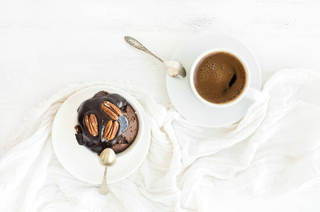 Tasty homemade brown muffin with chocolate ganache icing and pecan nuts cup of black coffee