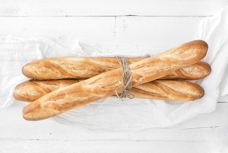 Freshly baked French baguettes on white wooden table