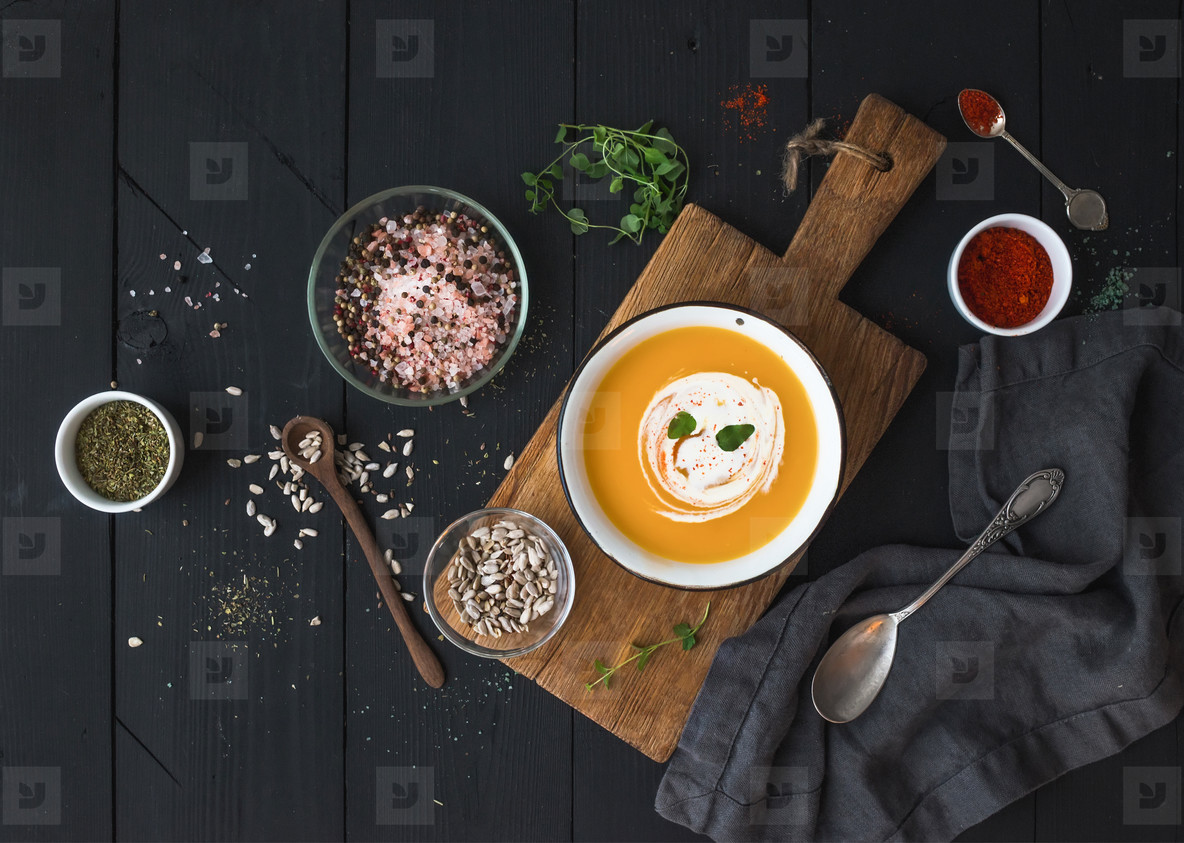 Pumpkin soup with cream  seeds and spices in rustic metal bowl