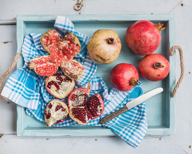 Red and white pomegranates with knife