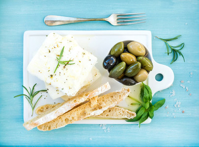 Fresh feta cheese with olives  basil  rosemary and bread slices
