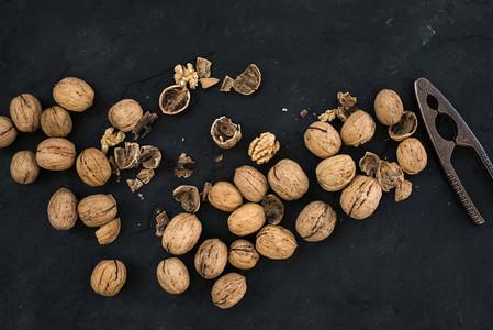 Walnuts with nutcracker over black slate stone background