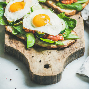 Bread toasts with fried eggs and fresh vegetables  square crop