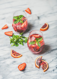 Orange and strawberry summer Sangria in glasses  marble background