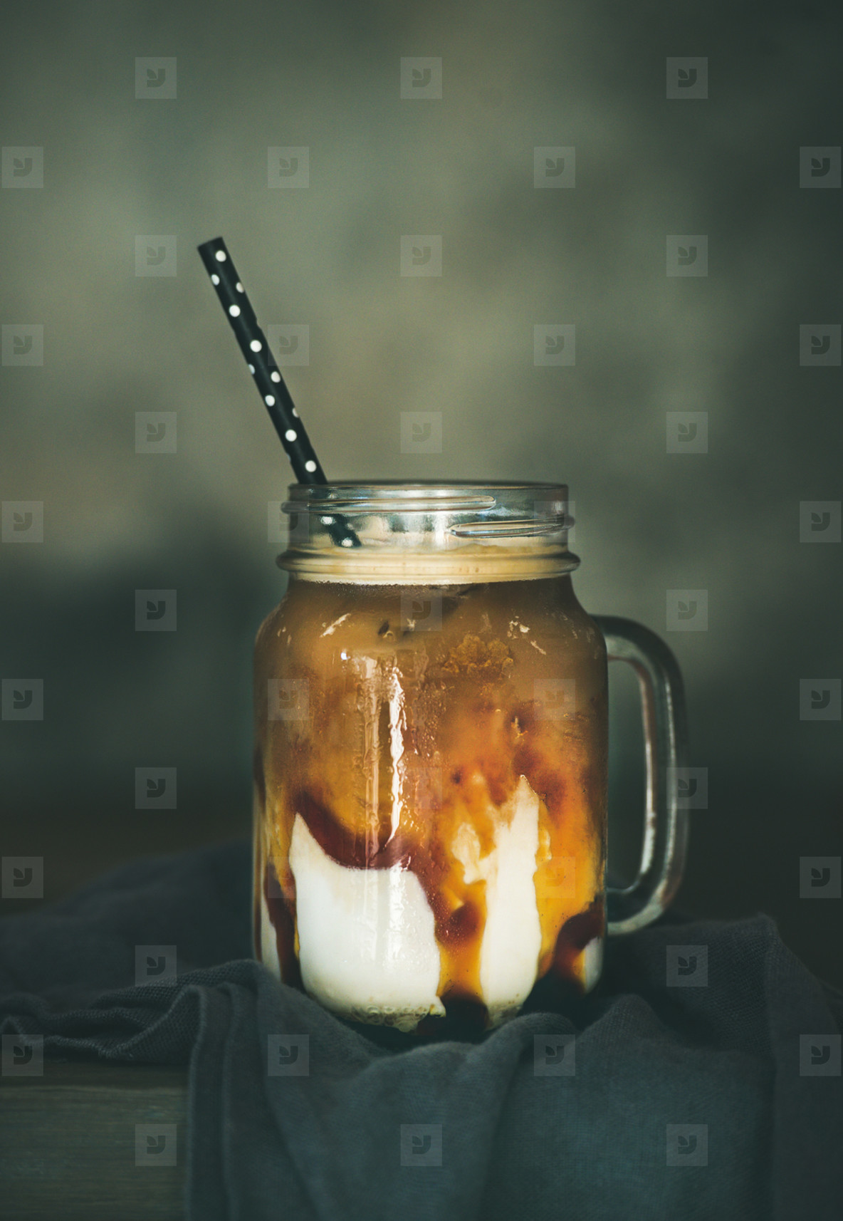 Iced caramel macciato coffee with milk in jar on table