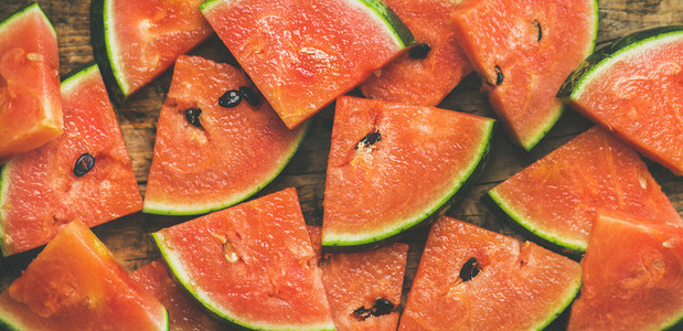 Juicy fresh watermelon pieces on rustic wooden background