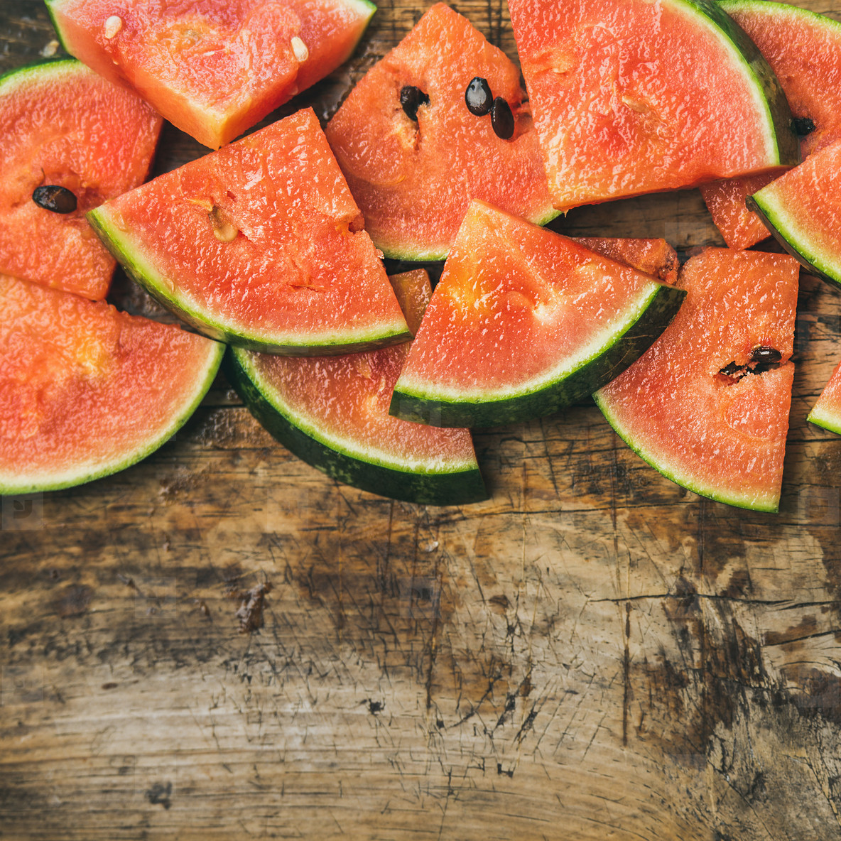 Juicy watermelon pieces over rustic wooden background  square crop