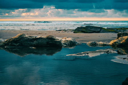 Beach with rocks and puddle in a sunset ribadeo spain