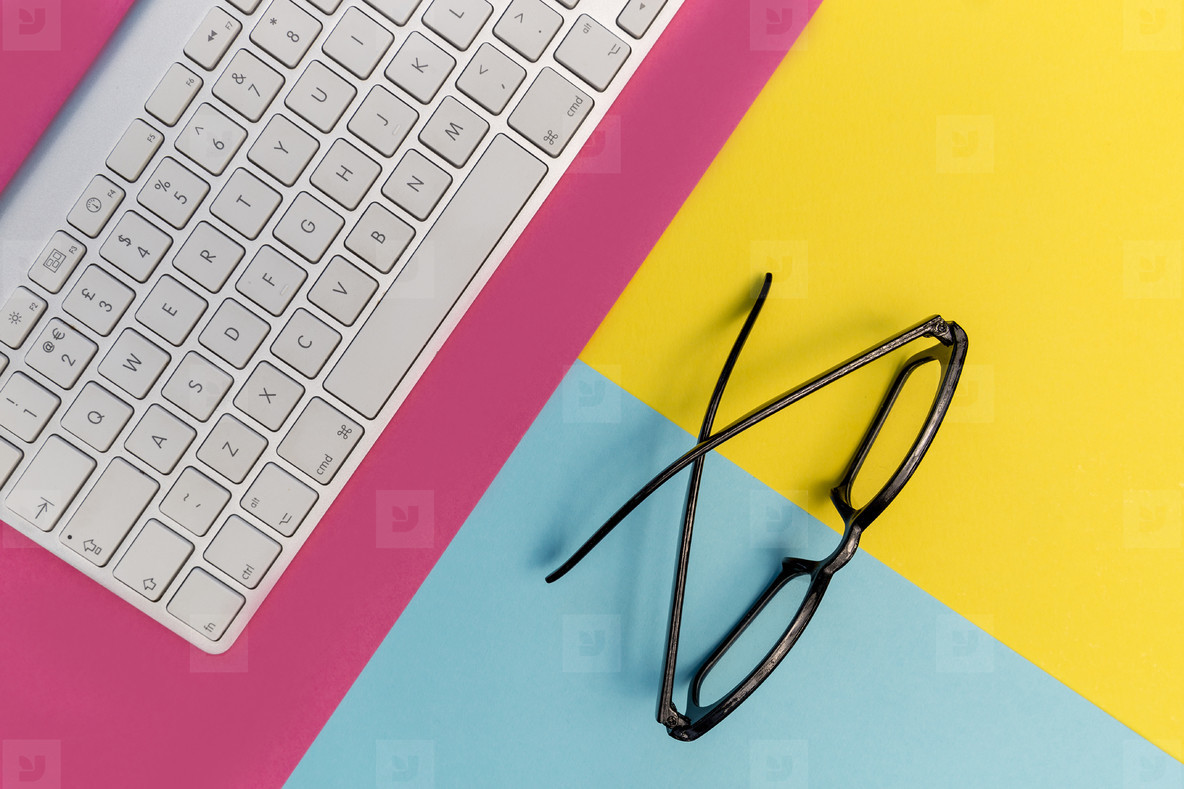 Computer keyboard eyeglasses on pink yellow background