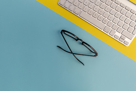 Computer keyboard eyeglasses on yellow blue background