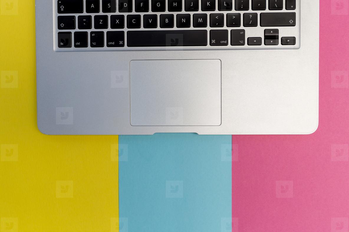 Laptop computer keyboard on pink blue background
