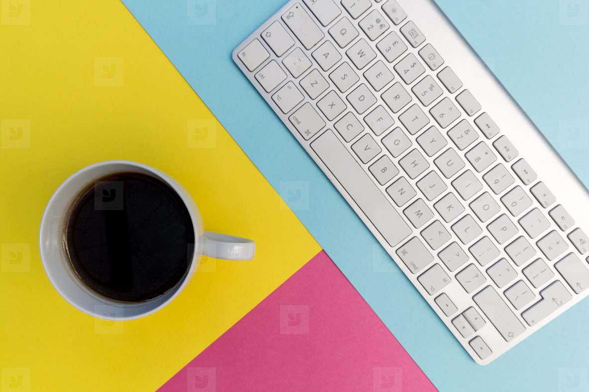 Computer keyboard coffee on pink yellow background
