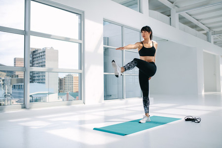Healthy woman doing stretching at gym
