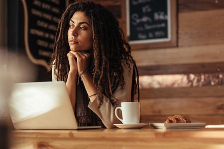 Freelancer woman sitting at a cafe with her laptop computer