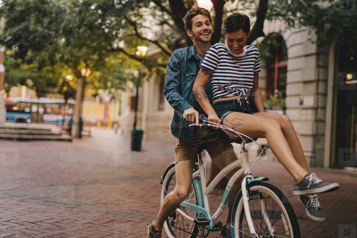 Happy couple on a bicycle in the city