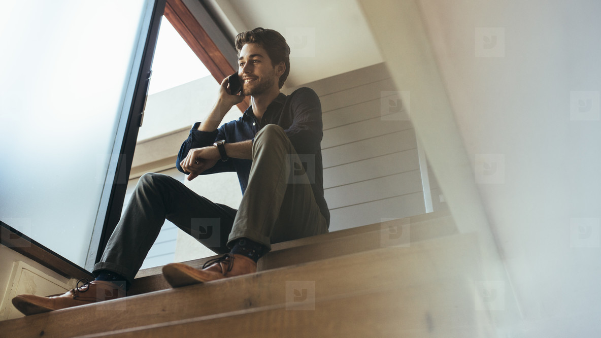 Man talking over mobile phone sitting at home