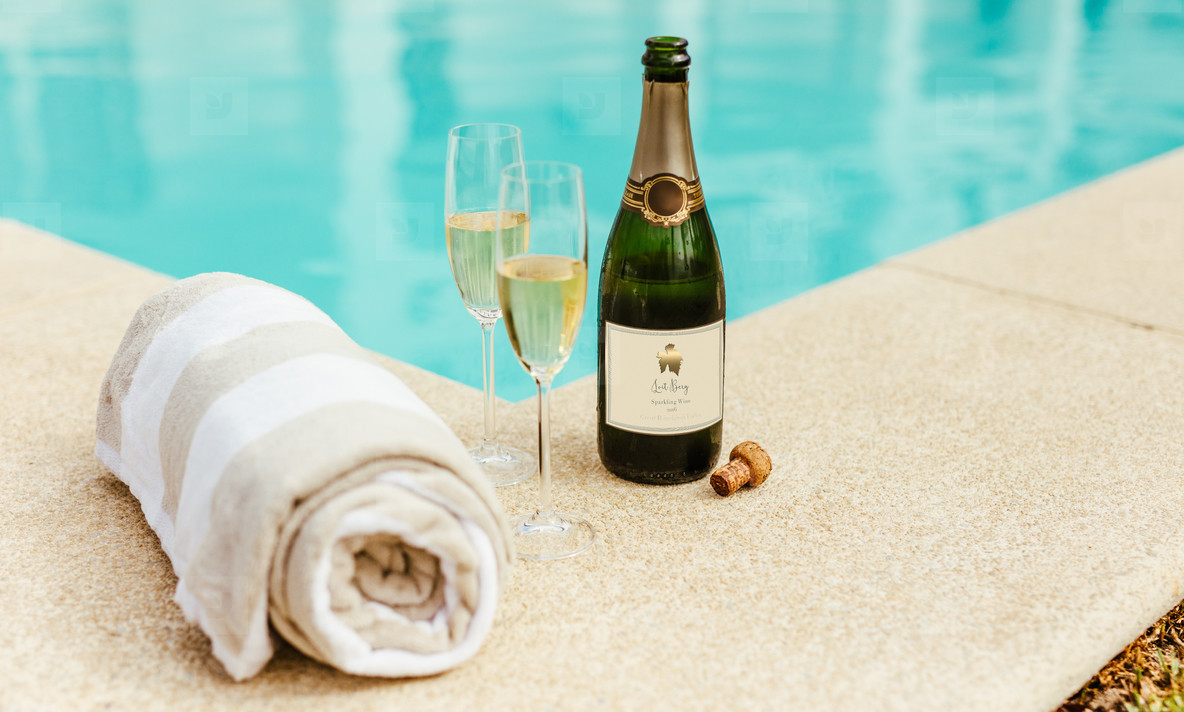 Sparkling wine and towel by the pool