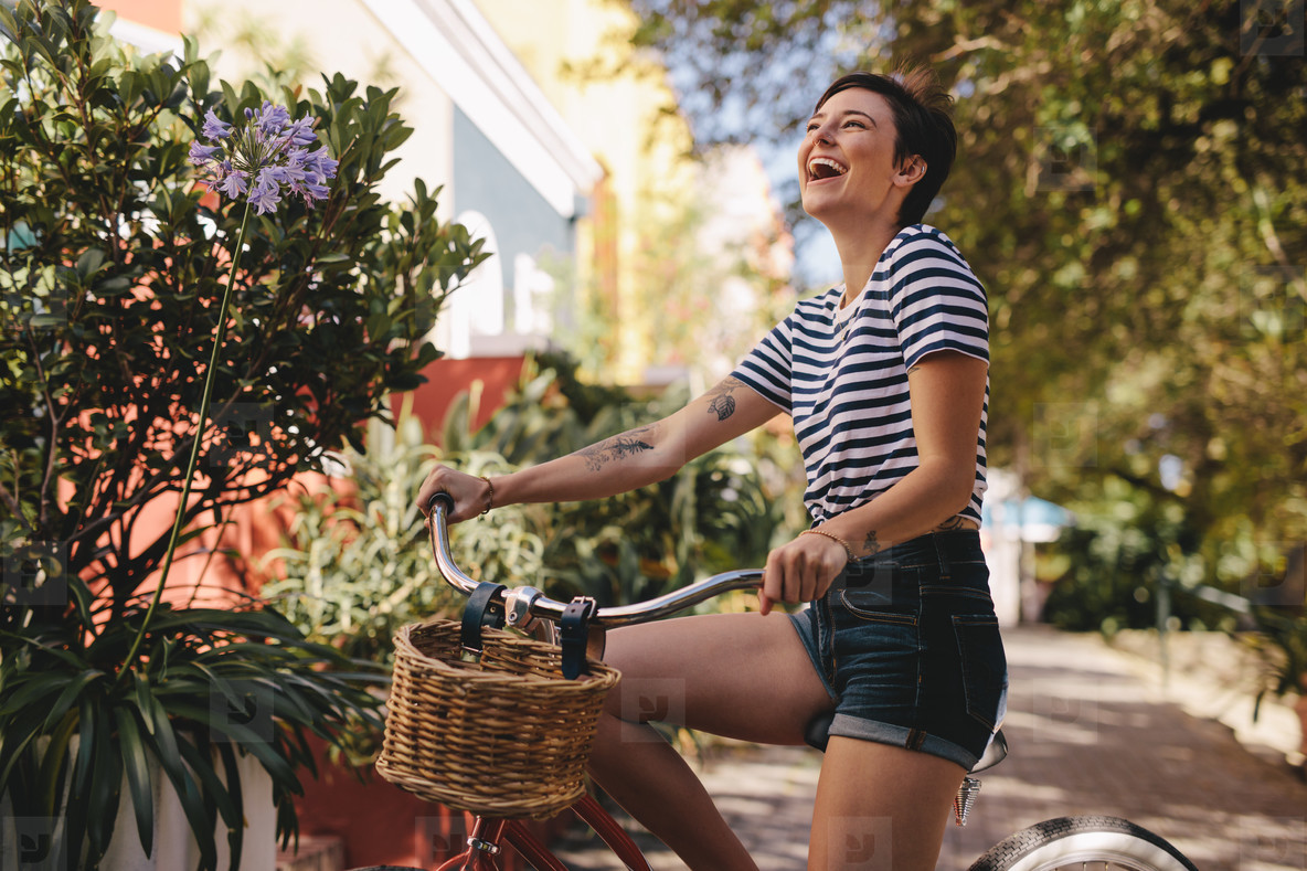 Laughing woman riding a bike in the city