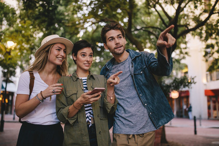 Friends using smartphone for find a way in city