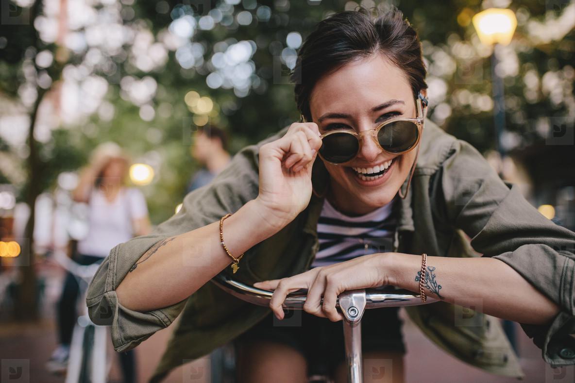 Cheerful woman in sunglasses with bike