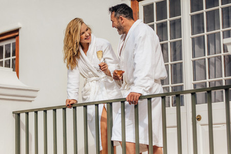 Couple in bathrobes drinking wine on balcony
