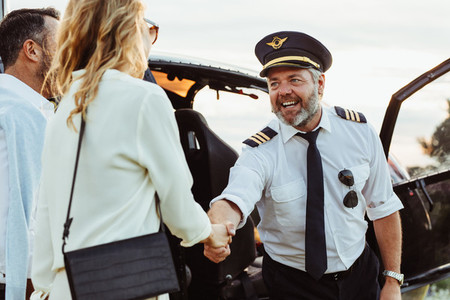 Helicopter pilot shaking hands with couple