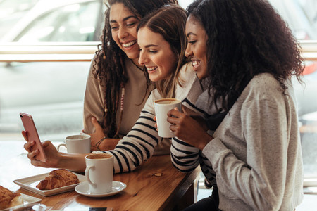 Friends sitting in a cafe looking at mobile phone