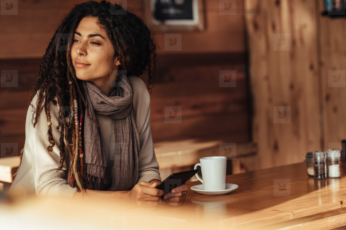 Woman sitting in a cafe holding her mobile phone