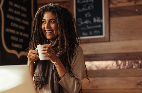 Woman enjoying a cup of coffee at a cafe