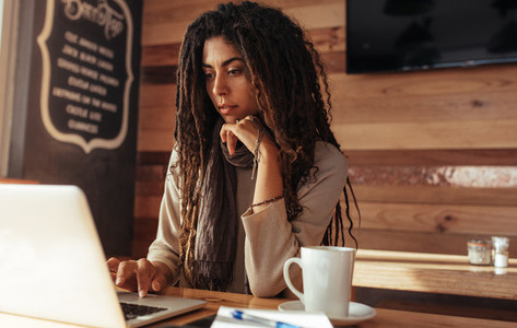 Freelancer woman working on laptop computer in a cafe