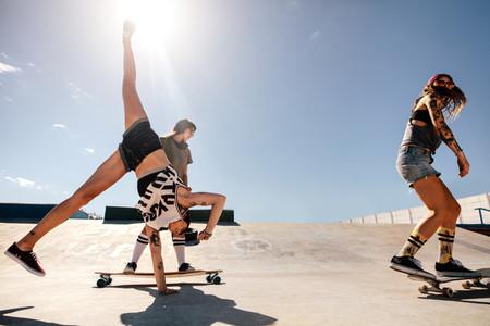 Females skateboarding and doing stunts at skate park