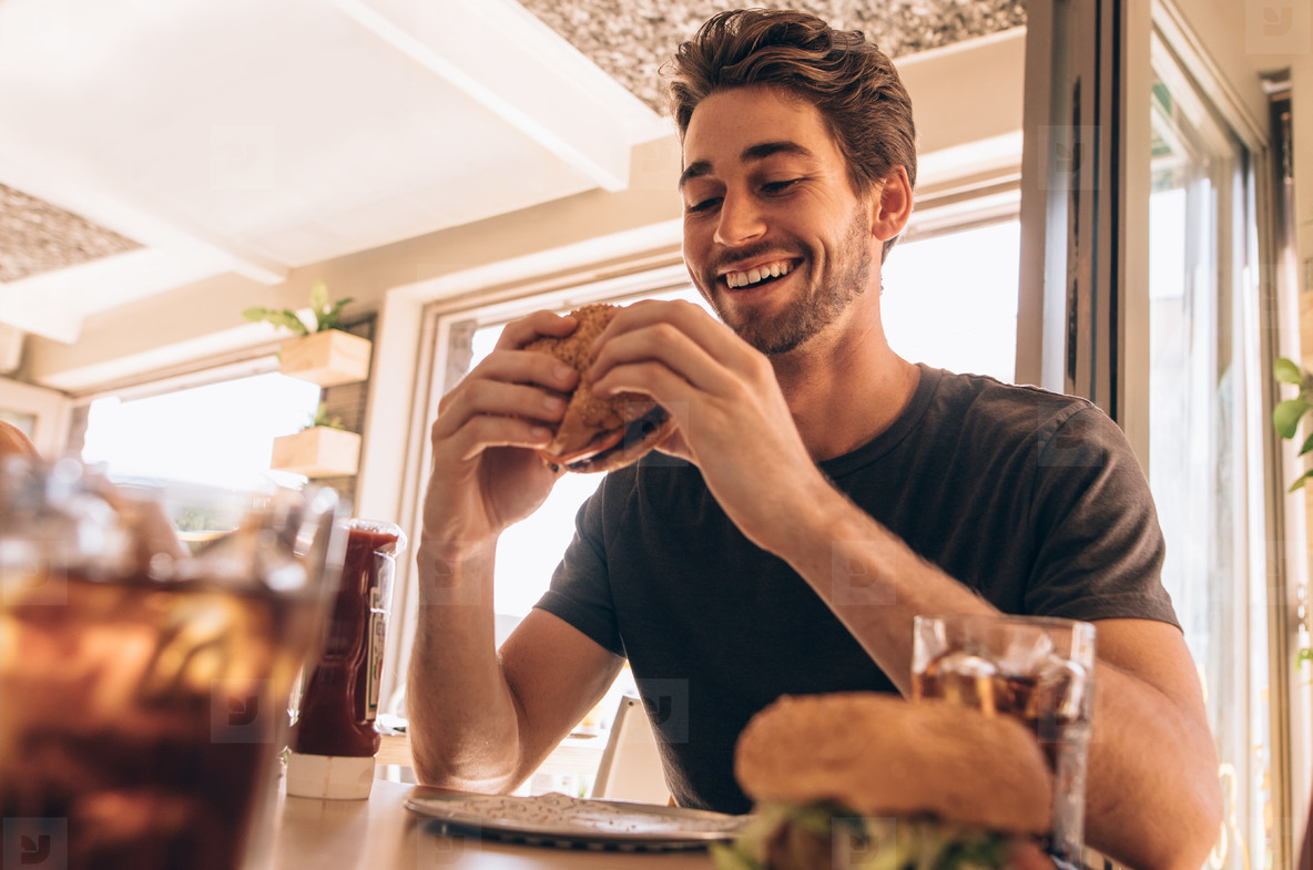 Young guy having stacked burger