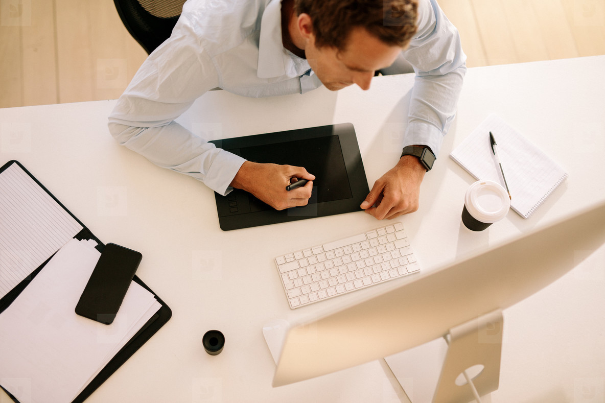 Top view of man using digitizer to write text in computer