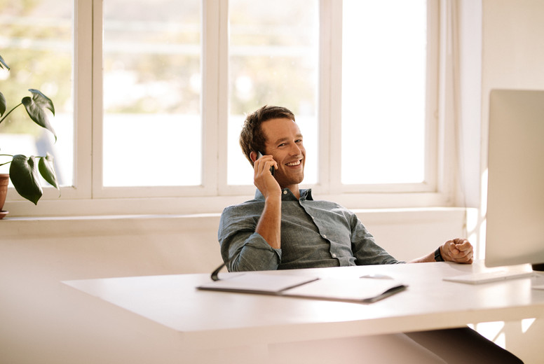 Entrepreneur talking on mobile phone while working on computer a