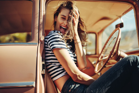 Laughing young woman sitting in the car