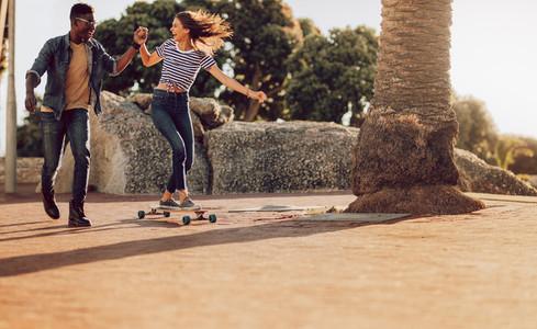 Woman skating on sidewalk with friend