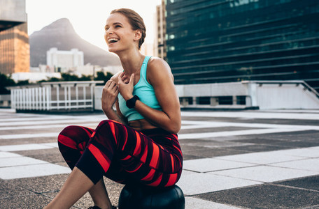 Smiling sportswoman resting on medicine ball