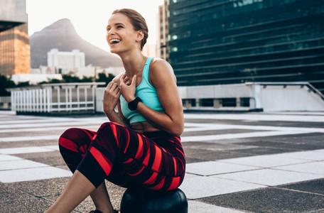 Smiling sportswoman resting on medicine ball